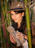 Pretty adventurer with stolen relic. In thick green bamboo forest royalty free stock image