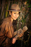 Pretty adventurer with stolen relic. In thick green bamboo forest royalty free stock photos