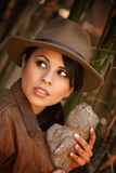Pretty adventurer with stolen relic. In thick green bamboo forest Stock Photos