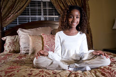 Pretty African American child. Cute 10 year old African American girl sitting on bed Royalty Free Stock Image