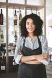 Pretty African American girl in apron standing with clasped hands in restaurant. Young girl with dark curly hair royalty free stock images