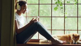 Pretty African American girl is listening to music with headphones and using smartphone sitting on window sill with. Pretty young African American girl is stock video