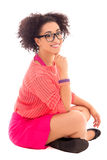 Pretty african american teenage girl in pink sitting isolated on Royalty Free Stock Images