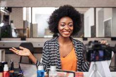 Pretty african american woman with curly hair looking wonderful. Pretty woman. Pretty african american woman with curly hair looking wonderful while recording a royalty free stock photos