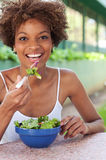 Pretty African American woman eating a salad Stock Images