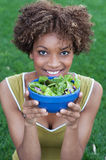 Pretty African American woman eating a salad. Pretty African American women with a healthy salad in a park Stock Image