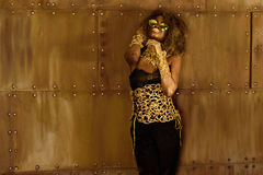 Pretty African American woman with golden makeup and sunglasses holding hands near face in front of bronze wall Royalty Free Stock Photo