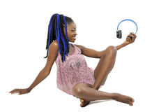 Pretty African American woman holding a headphone. Pretty young African American woman admiring a headphone Royalty Free Stock Image