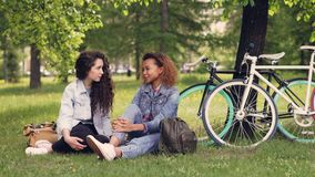 Pretty African American woman is talking to her European friend in park sitting on grass, girls are chatting and. Laughing. Bikes and trees are in background stock video