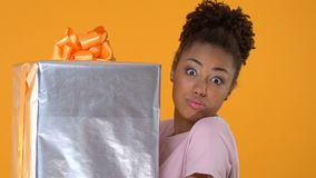 Pretty african female hardly holding big present box on bright background, gift. Stock footage stock video