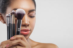 Pretty african girl is doing facial make-up Royalty Free Stock Photography