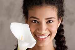Pretty african girl smiling, holding white flower over beige background. Stock Photos