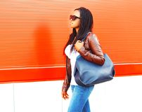 Pretty african woman with bag walking in city over red Royalty Free Stock Photo