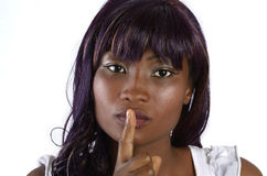Pretty african woman with finger before mouth. Studio shot, closeup, Cameroon Royalty Free Stock Photos