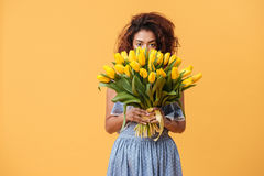 Pretty African woman hiding behind bouquet of flowers Royalty Free Stock Photography