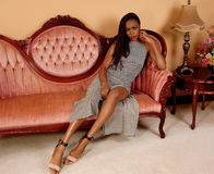 Pretty African woman on pink couch. Royalty Free Stock Images