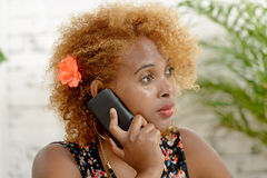 A pretty African woman with red hairs, phone Royalty Free Stock Photo