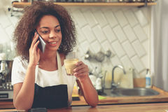 Pretty african woman speaking on mobile and holding latte royalty free stock images