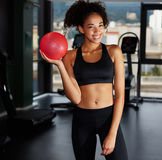 Pretty afro american girl holding pilates toning ball at gym Royalty Free Stock Images