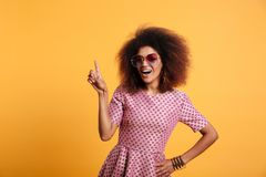 Pretty afro american retro woman with afro hairstyle pointing wi. Th finger up, looking at camera, isolated on yellow background Stock Photo