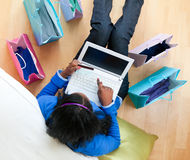 Pretty afro-american teen using a laptop at home Stock Photos