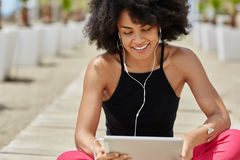 Pretty afro american woman listening audiobook on tablet smiling Royalty Free Stock Photos