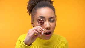Pretty Afro-American woman using eyelash curler, girls tips, evening make-up royalty free stock images