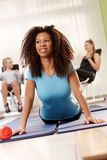 Pretty afro girl doing push-ups on exercise mat. Pretty afro girl exercising at the gym, lying on front, doing push-ups royalty free stock photo