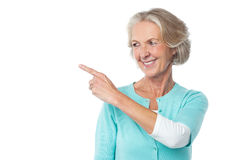 Pretty aged woman pointing at something Royalty Free Stock Image