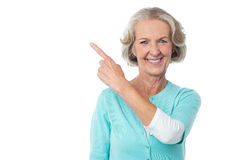 Pretty aged woman pointing at something Stock Images