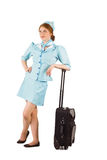 Pretty air hostess leaning on suitcase. On white background stock photography