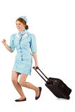Pretty air hostess pulling suitcase. On white background royalty free stock images