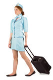 Pretty air hostess pulling suitcase. On white background stock image