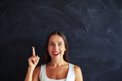 Pretty amazing young woman is pointing her finger up stock images