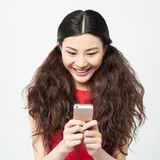 Pretty amused girl reading funny sms. Charming pretty girl reading messages royalty free stock photo
