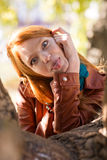 Pretty amusing redhead girl making funny face and showing tongue. Posing in park near tree stock photo