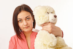 Pretty angry girl strangling teddy bear. Young pretty angry girl strangling teddy bear Royalty Free Stock Photo