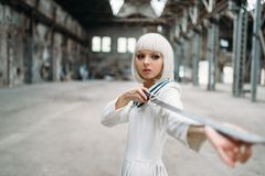 Pretty anime style blonde woman with sword. Cosplay fashion, japanese culture, doll with blade on abandoned factory, cute girl with makeup royalty free stock photo