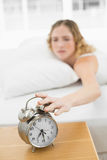 Pretty annoyed blonde lying in bed turning off alarm clock Stock Image
