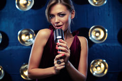 Pretty appealing woman singing with a microphone in a studio lig Royalty Free Stock Photography