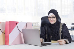 Pretty Arabic woman shopping online. Beautiful Arabic  woman smiling happy while using notebook and credit card for shopping online with shopping bags on the Stock Photo