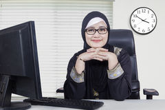 Pretty Arabic woman smiling in the office. Picture of Arabic young woman wearing headscarf and smiling at the camera while sitting in the office with computer on Royalty Free Stock Photos