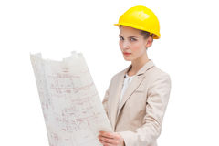 Pretty architect with helmet holding construction plan. An architect with yellow helmet holding construction plan and looking at the camera Royalty Free Stock Image