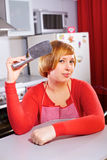 Pretty artful housewife with knife at kitchen Royalty Free Stock Images