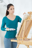Pretty artist painting on canva Royalty Free Stock Photos