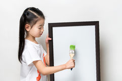 Pretty Asia little girl with a brush and white banner Stock Images