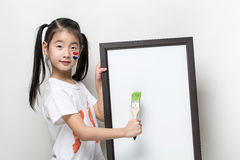 Pretty Asia little girl with a brush and white banner. Stock Images