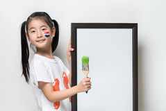 Pretty Asia little girl with a brush and white banner. Royalty Free Stock Photos