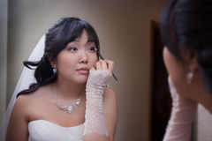 Pretty asian bride. Asian bride do make-up Royalty Free Stock Photography