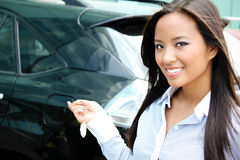A pretty asian business woman with her car. Young attractive asian businesswoman closes the door of her car stock photos